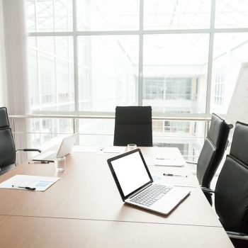 Modern office boardroom interior with laptops documents on conference table and big window, empty company meeting room with no people after corporate group briefing, business real estate for rent